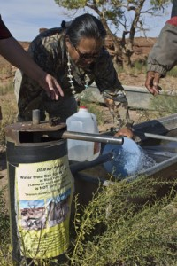 Earl Tulley fills containers with uranium-contaminated drinking water at Box Spring well in Black Falls, Ariz. Photo by Rachel Wise