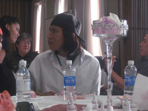 Aubrey Smith, dressed in a backwards cap and a button up T-shirt, sits back at a Navajo wedding. photo by Lauren Gerber