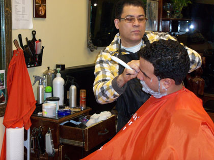 Jose Taveras gives Jay Hernandez a shave inside Groom Team barbershop in Washington Heights. Taveras contends Dominicans and Haitians no longer bare resentment toward one another, but other Dominicans disagree. (Photo by Simon McCormack)