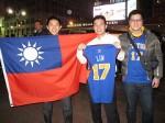 Kuan-sseng Wu (center), 23, a student from Taiwan, shows off his Jeremy Lin jersey while posing alongside the Taiwanese flag. Photo by Louie Lazar.