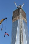 A flag is suspended from a crane next to 1 World Trade Center, the building formerly known as the Freedom Tower. by Alyana Alfaro