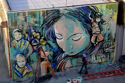 Artist Alice Pasquini is shown painting her latest mural. She traveled from Rome to be a part of the Bushwick magnet. Photo by Gabrielle A. Wright.