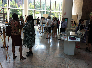 Visitors browse the art exhibit at the Bellevue Hospital center featuring work by World Trade Center survivors. Photo Credit: Leticia Miranda.