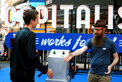"Artist Steve Lambert shakes the hand of a curious pedestrian at his ""Capitalism works for me!"" exhibit in Times Square yesterday. Photo by Zoe Lake."