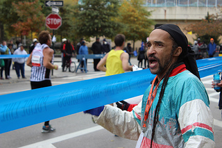 Keith Williams, 59 of West Harlem encouraged runners with cheers and ringing a bell for each one that passed by. Photo by Alexandra Palmer