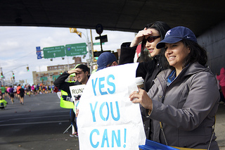 Karin Ortiz, of East Harlem, holds a sign to encourage her four friends running the marathon. Photo by Léa Bouchoucha