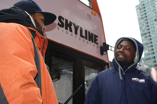 Tour bus ticket vendor Amara Fofana (right) talks to supervisor Johnny Morales (left) outside a tour bus in Times Square as temperatures start to drop. Photo by Rajeev Dhir.