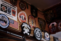 The walls of O'Hara's Pub, NYC, covered in patches from twelve years of first responder gatherings on 9/11. Photo by Thom Friend.