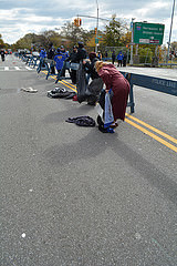 Just before the next wave of marathon runners came, Pat Corsilli, 64, collected clothing thrown by the previous runners. Photo by Virginia