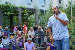 Ray Figueroa, president of the NYC Community Gardens Coalition, addressing the crowd assembled to mourn the passing of Adam Purple, urban gardener and activist. Photo by Diego Lynch