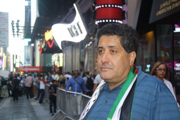 Diab Mustafa, President of the Palestinian American Community Center, stands at the back of the demonstration, wearing a Palestinian flag. Photo by Wyatt Salsbury