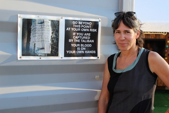 Photojournalist Rita Leistner pauses for a moment at Photoville outside of a shipping container that showcases the work she photographed entirely on her smart phone while embedded with U.S. Marines in Afghanistan in 2011. Photo by Elizabeth Arakelian