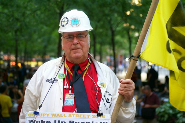 Chuck Helms, a member of International Brotherhood of Electrical Workers. He was covered in pro-union ephemera, including the flag, buttons, and embroidery on his clothing. He had been attending Occupy Wall Street since September of 2011, and now comes to Zuccotti Park every Friday. Photo by Diego Lynch