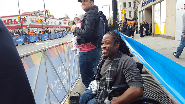 Ricky Dick smiles as the New City Marathon participants pass by. It's his first year attending the marathon. Seeing other's with disabilities participate have inspired him, he said. Photo by Taisha Henry.
