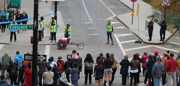 People gathered at the corner of Crescent Street and Queens Plaza South in Long Island City, Queens, cheer as one of the wheelchair racers passes through. Photo by Karis Rogerson.