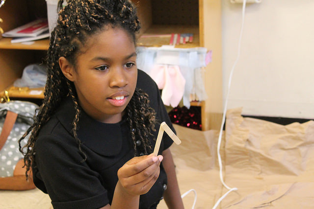 Brittney Rodriguez, 11, is making stick figures out of popsicle sticks to add to her 3D demonstration of what her birthday party will look like. Photo by Karis Rogerson