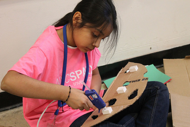 "Pamela Flores, 11, uses a hot glue gun to put together a backdrop for an ""Angry Birds"" project at NYC Sparx. Photo by Karis Rogerson."