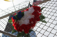 An American flag and order of flowers hung on a fence outside of the World Trade Center Site. Photo by Brelaun Douglas.