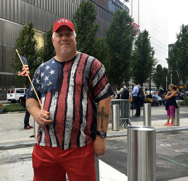David Sears standing outside the 9/11 memorial waving his American flag. Photo by Jennifer Cohen