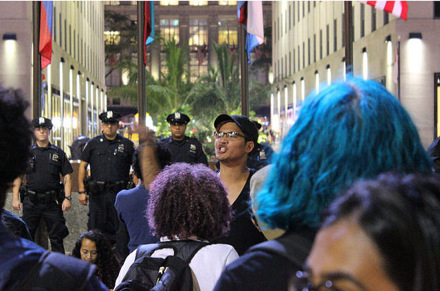 After the one mile march, leading member of Hoods4Justice spoke to the crowd of demonstrators in Rockefeller Plaza on Saturday night as NYPD officers stood along the perimeter. Photo by Brandon Gomez.
