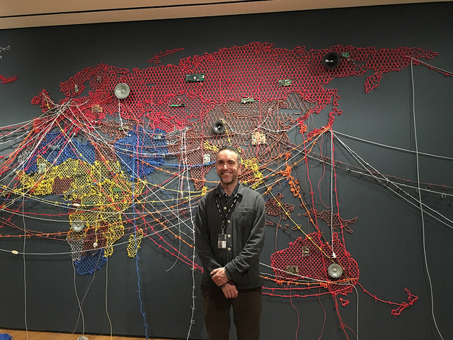 Sean Anderson, associate curator in the Department of Architecture and Design at MoMA, is standing in front of the eye-catching and creative map representing the global refugee crisis. Photo by ANG LI.