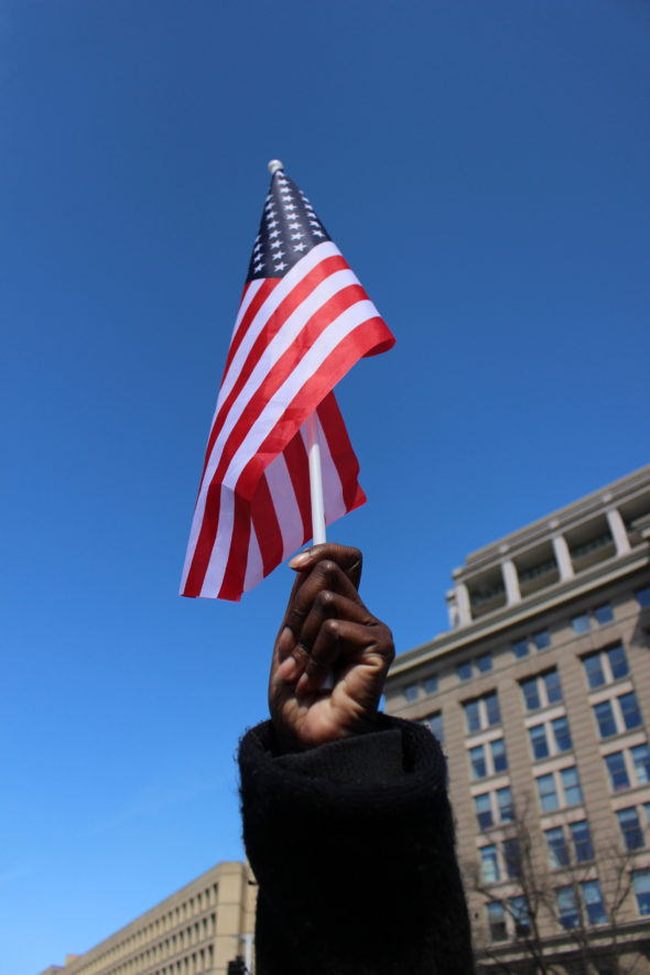 A protester waves an American flag as she marches at the March for Our Lives in Washington, D.C.